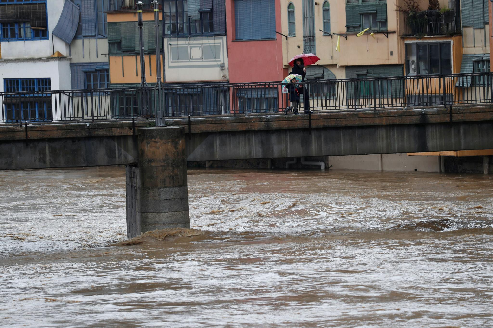 "Residents walk on a bridge on the Onyar river during the storm ""Gloria"" in Girona"
