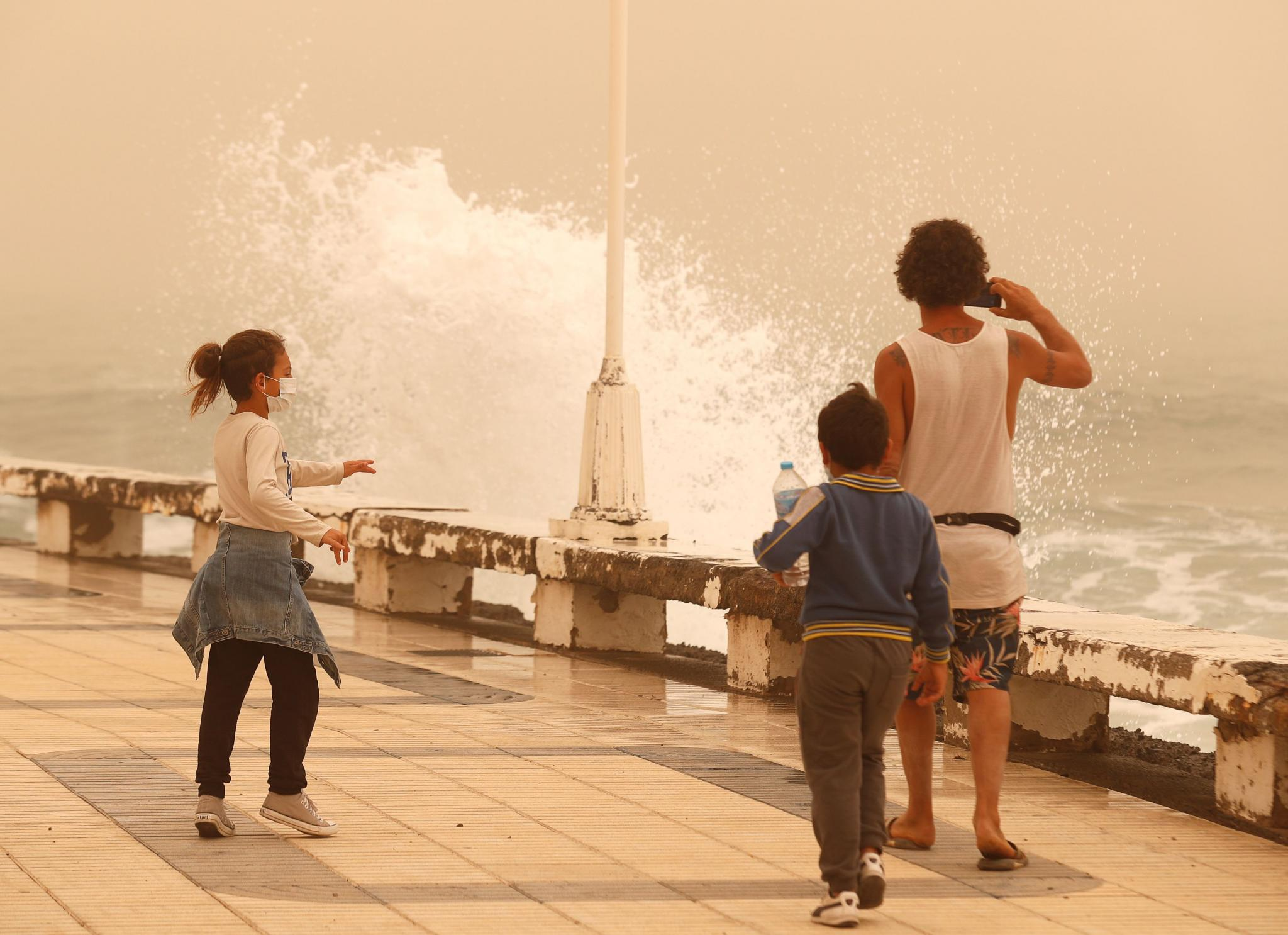 """A family watches the waves during a sandstorm locally known as """"calima"""" in the Canary Islands, Gran Canaria"""