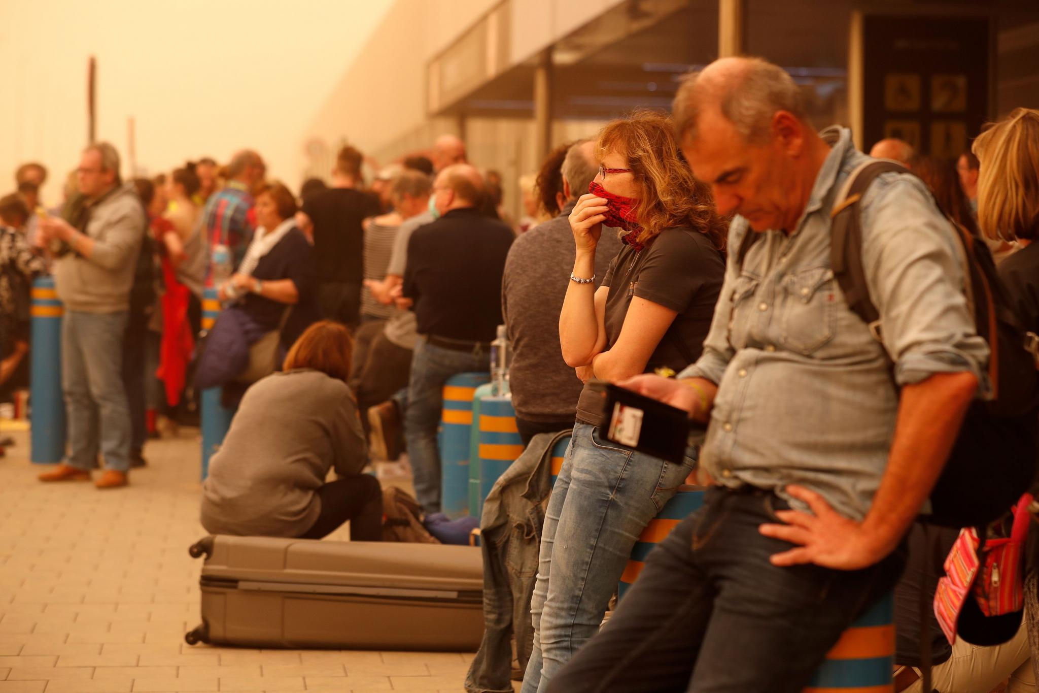 """Stranded passengers wait at Las Palmas Airport in Gran Canaria, as a sandstorm locally known as """"calima"""" closed air traffic in the Canary Islands"""