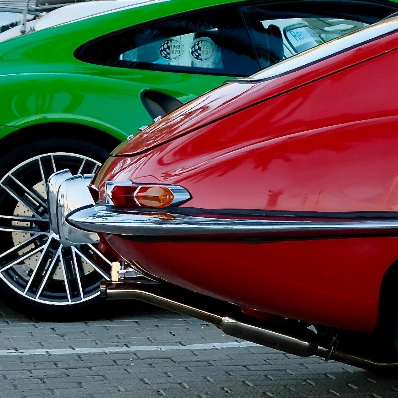 This photo has it all: composition, colour, light. Red E-Type & fluorescent Porsche 911