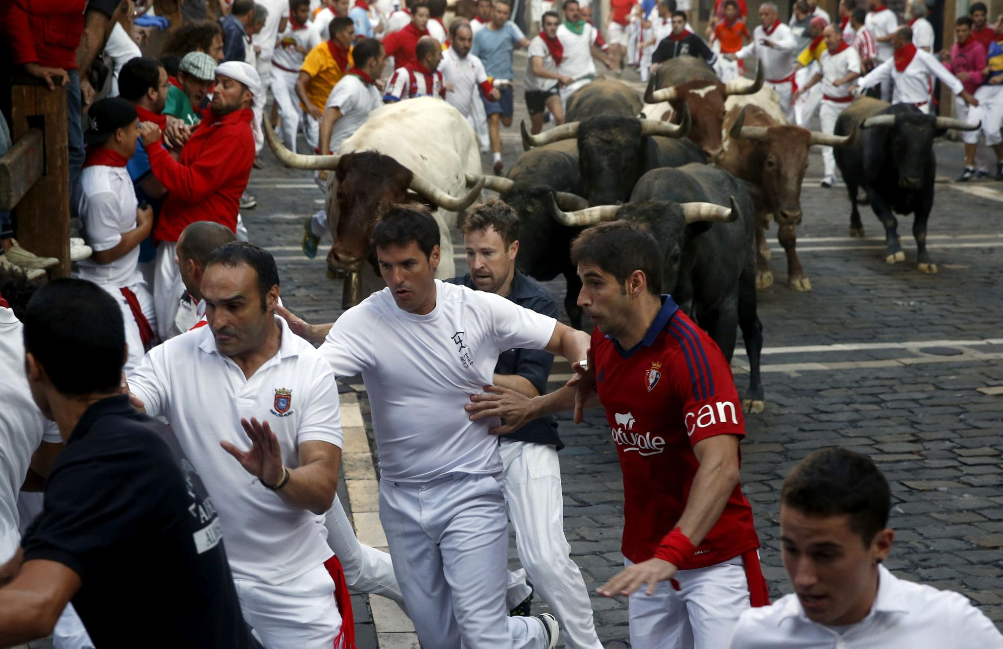 FILE PHOTO: Runners lead Miura fighting bulls during the last day of the running of the bulls of the San Fermin festival in Pamplona