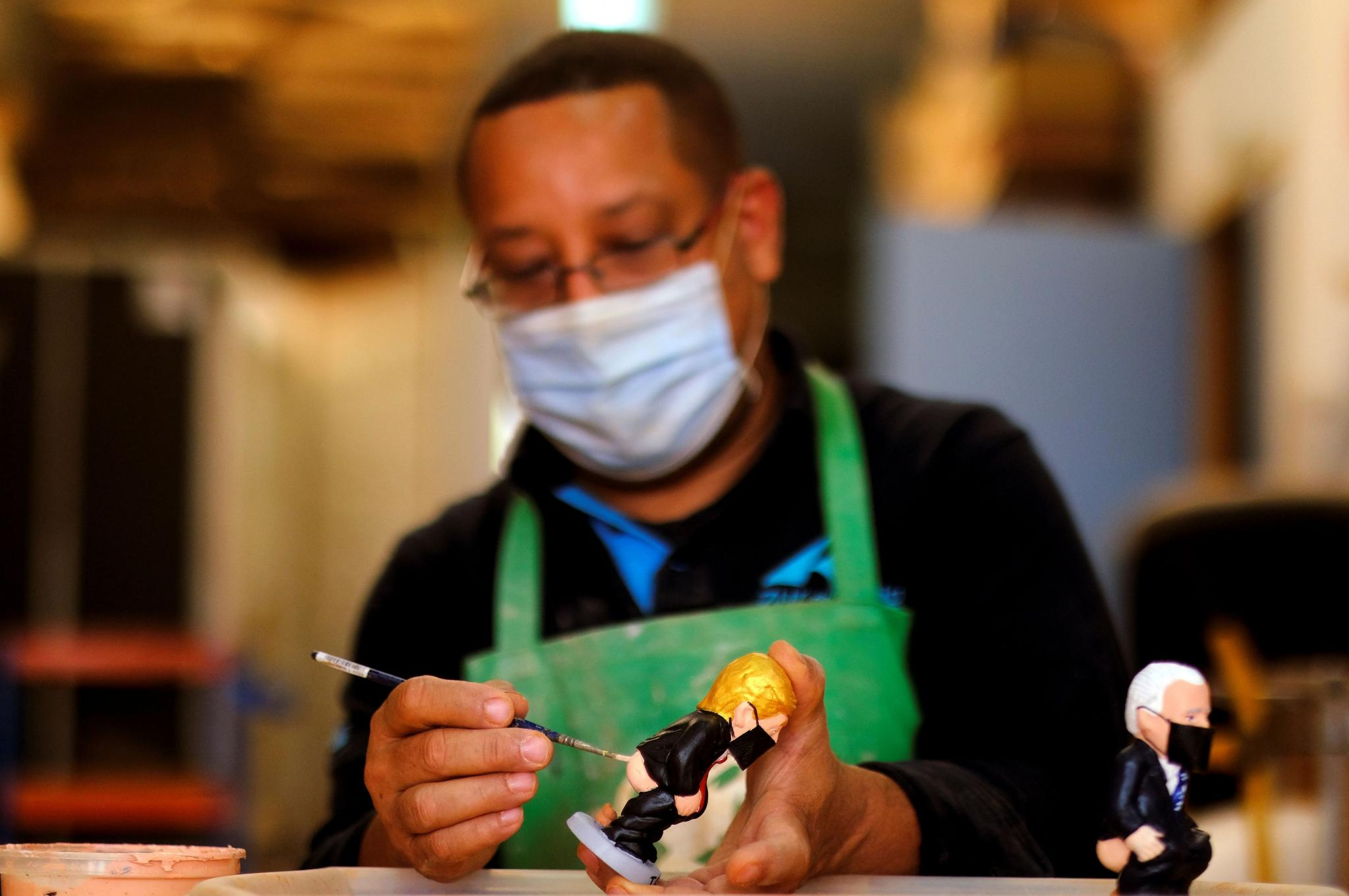 """A worker paints a U.S. President Trump """"caganer"""", in a pottery in Torroella de Montgri"""