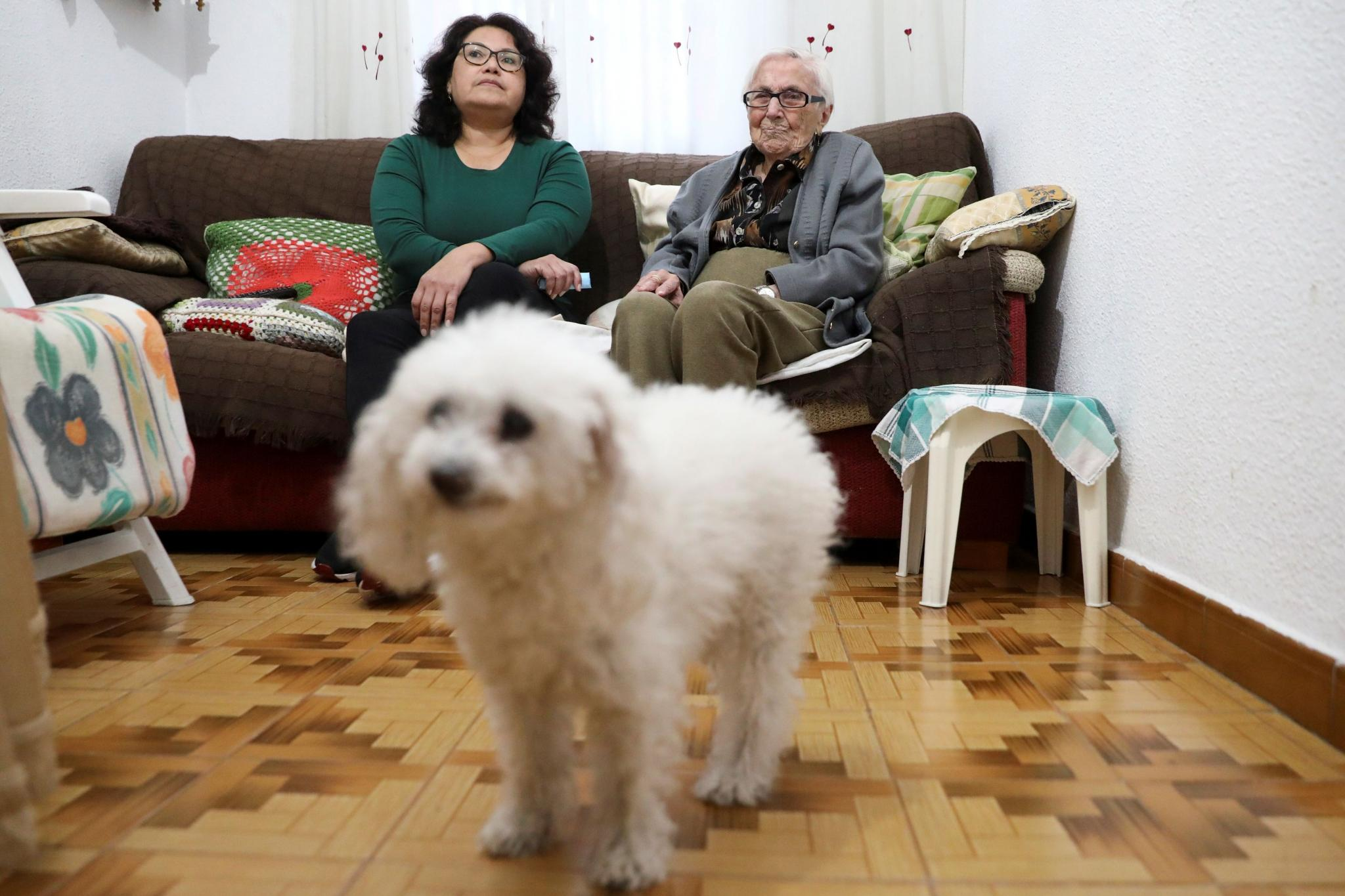 Florentina Martin, a 99 year-old woman who survived coronavirus disease (COVID-19), sits on a sofa with her caregiver Olga Arauz as they watch TV at her home in Pinto