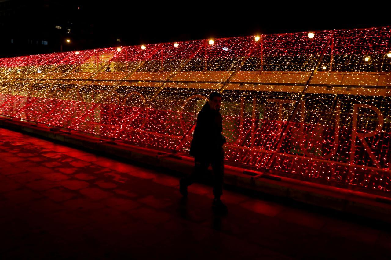 Un hombre pasa junto a una parte de un kilómetro de luces navideñas con los colores de la bandera española en Madrid.