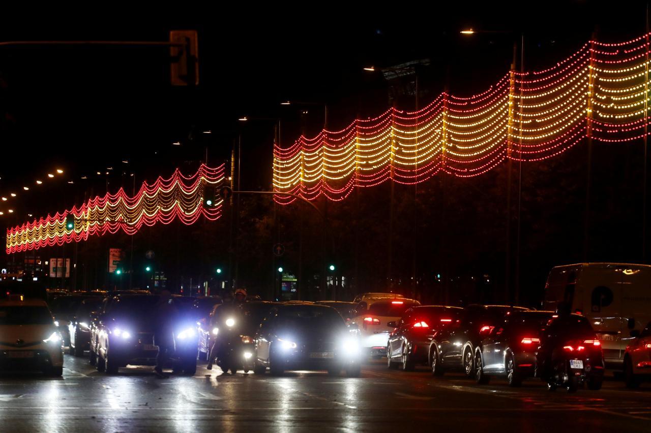 Los coches se ven bajo una parte de una iluminación navideña de un kilómetro de largo con los colores de la bandera española en Madrid.