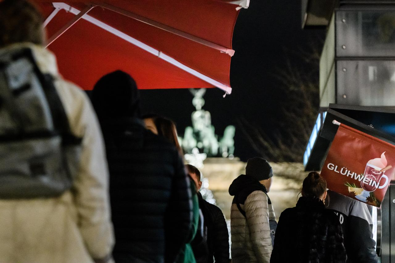 People queue up at a mulled wine stand in front of the Brandenburg Gate in Berlin