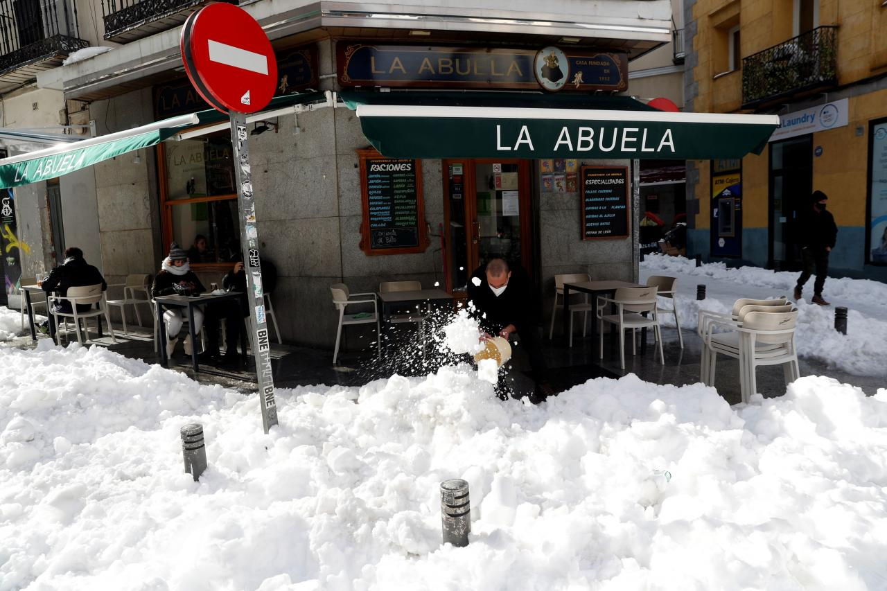 An employee of a restaurant clears snow as customers sit at an outdoor terrace in Madrid