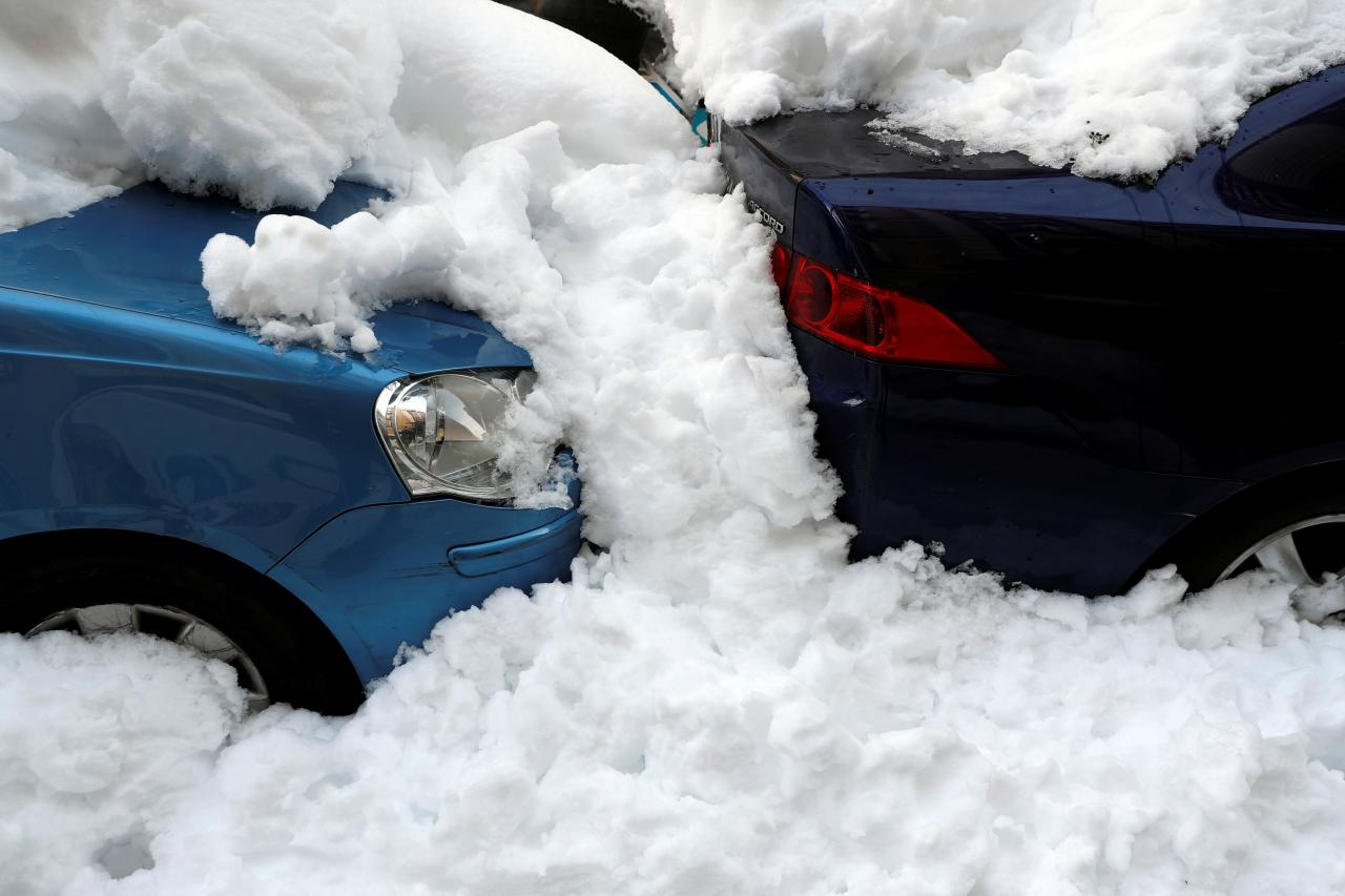Snow covers cars on the street in Madrid