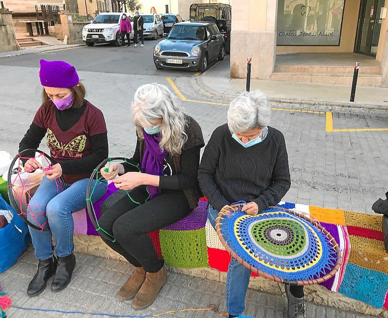 'Teixits de Sororitat' members weaving an awning against sexist violence for International Women's Day.