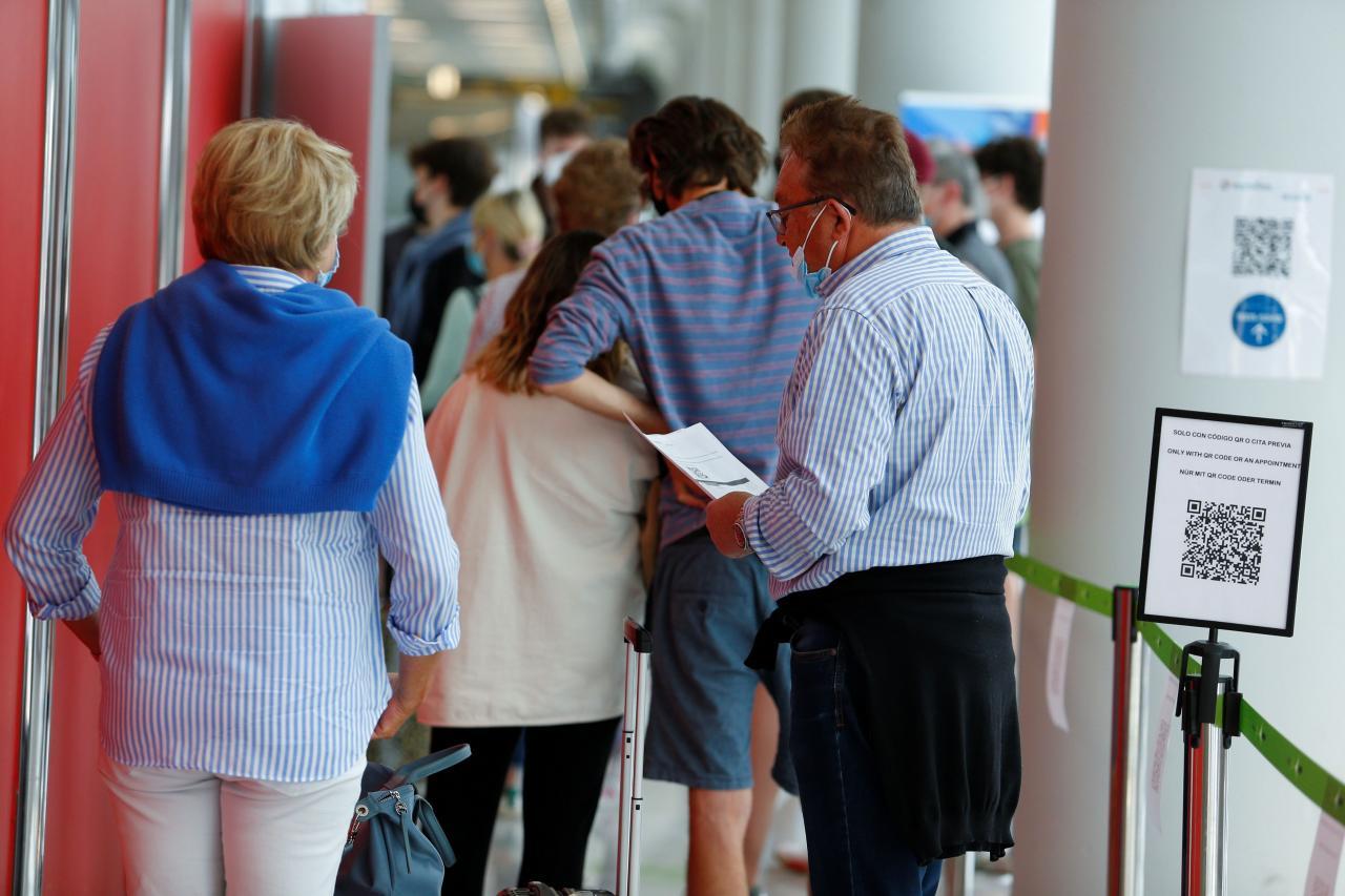 People queue outside a coronavirus disease (COVID-19) test site at Son Sant Joan airport in Palma de Mallorca