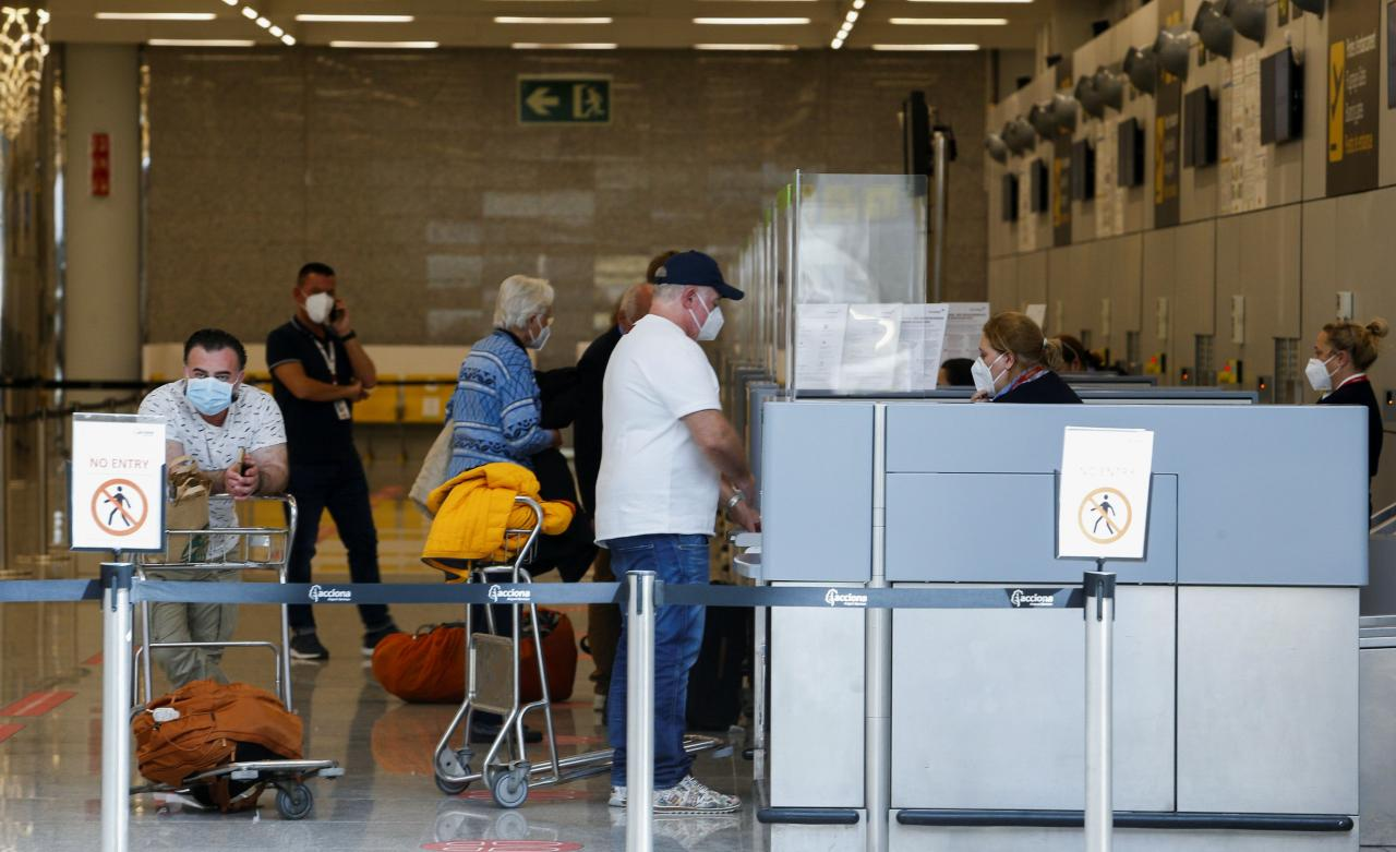 People stand at the check-in counters at Son Sant Joan airport in Palma de Mallorca