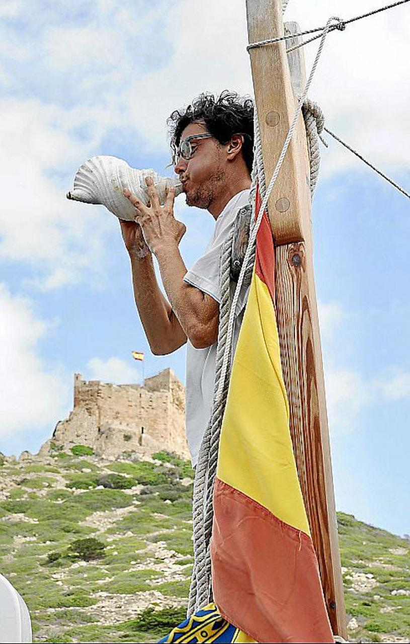 A man blowing a conch shell at the Anniversary event in Cabrera.