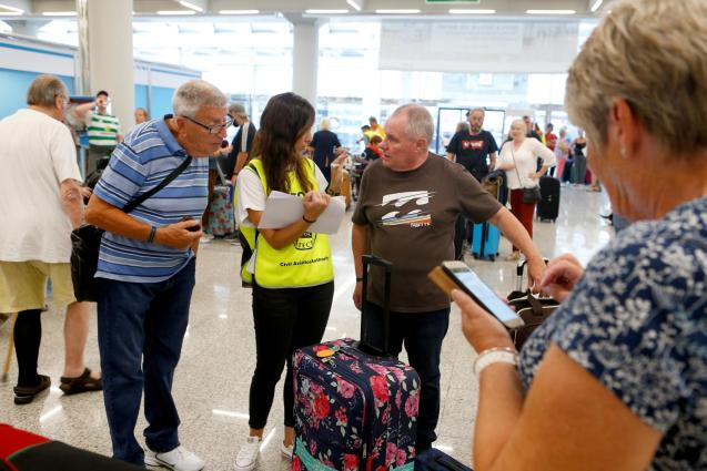 Passengers talk to Civil Aviation Authority employee at Thomas Cook check-in points at Mallorca Airport after the world's oldest travel firm collapsed, in Palma de Mallorca