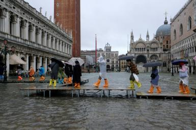 People walk on a catwalk in the flooded St.Mark's Square during a period of seasonal high water in Venice, Italy November 12, 2019.