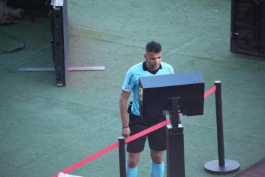 Referee Manzano consulting the VAR screen.