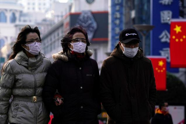 People wearing protective masks walk at the Nanjing Road in Shanghai, China January 29, 2020.