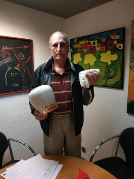 Gerg with the broken urn where he kept his mother's remains and the remaining ashes in a bag