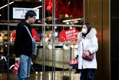 A tourist wears a protective mask as she leaves the Galeries Lafayette department store in Paris as the country is hit by the new coronavirus, France, January 30, 2020.