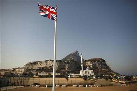 A Union flag flies at Europa Point in front of the Rock (rear), a monolithic limestone promontory