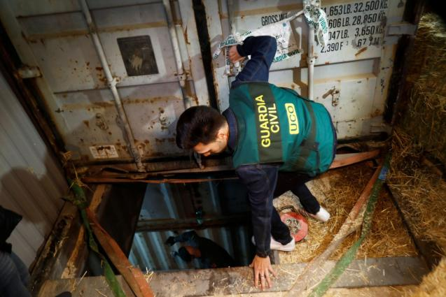 A Spanish civil guard enters an illegal underground tobacco factory during a police raid in Monda