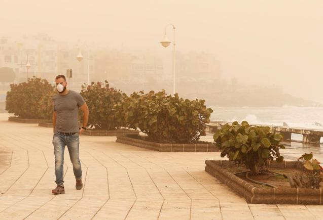 """A man walks around with a mask on during a sandstorm locally known as """"calima"""" in the Canary Islands, Gran Canaria"""