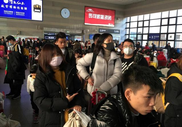 Passengers wearing masks wait to board trains at the Beijing West Railway Station