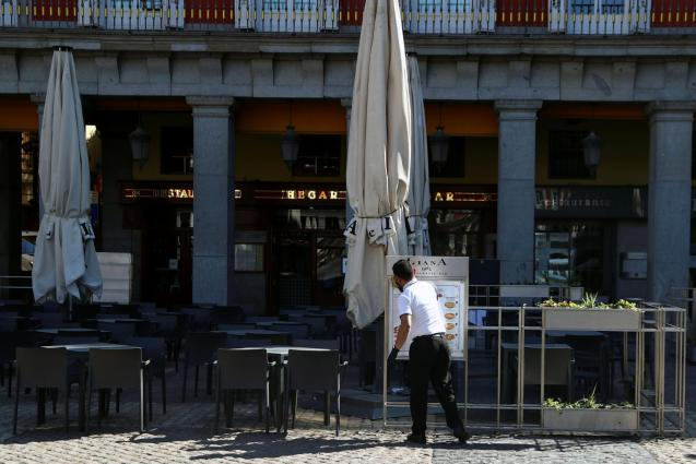 A worker cleans an empty terrace in unusually quiet Plaza Mayor in central Madrid