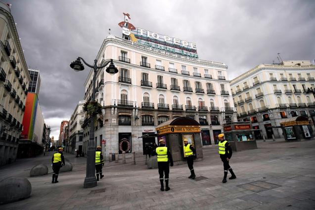Members of the Military Emergency Unit patrol in an almost empty Puerta del Sol, Madrid