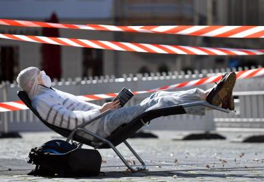 A man, wearing a protective mask, glasses and a suit is reading a book in the sun during a partial lockdown in Dresden, Germany, March 23, 2020, as the spread of the coronavirus disease (COVID-19) continues.