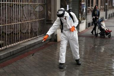 A municipal worker in protective gear disinfects a street during the coronavirus disease (COVID-19) outbreak in Madrid, Spain March 23, 2020.