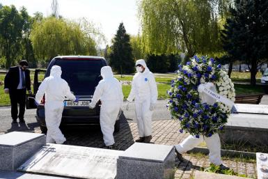 Municipal workers wearing protective gear carry a wreath for a victim of coronavirus disease (COVID-19) at El Salvador cemetery in Vitoria, Spain, March 27, 2020.
