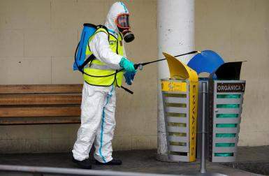 A member of the Royal Guard wearing protective gear sanitises a dumpster outside the emergency unit at 12 de Octubre Hospital, amid the coronavirus disease (COVID-19) outbreak in Madrid, Spain March 30, 2020.