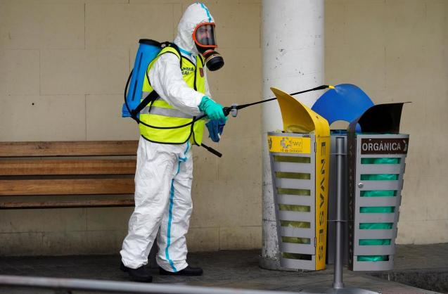 A member of the Royal Guard wearing protective gear sanitises a dumpster