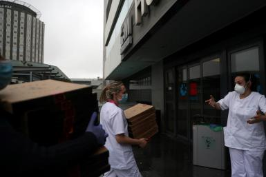 Medical staff at La Paz Hospital carry the 20 pizzas being delivered as part of the Food4Heroes initiative during the outbreak of coronavirus disease (COVID-19) in Madrid, Spain, March 31, 2020.