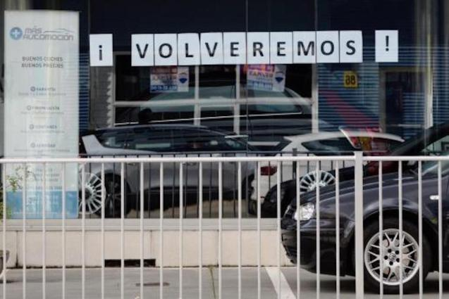 A 'We will return!' sign in the window of a car dealership in Valladolid.