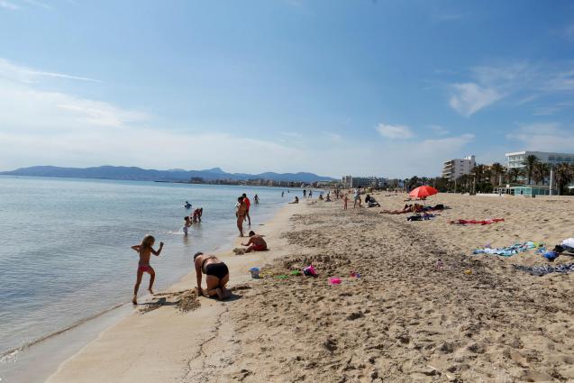 People sunbathe on El Arenal beach.