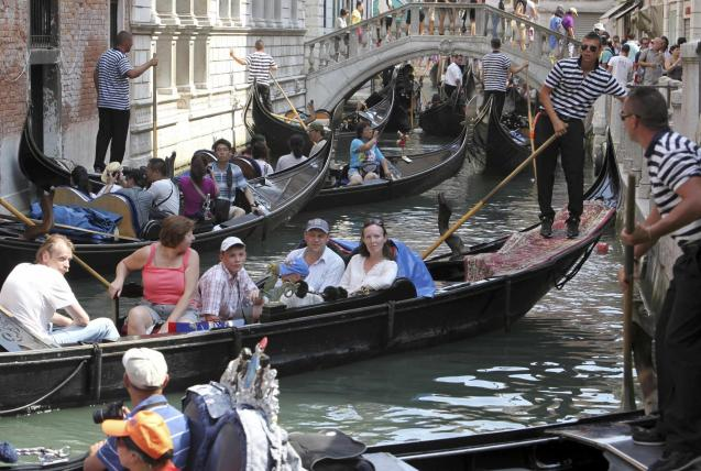 Gondoliers row gondolas full with tourists on a busy canal in Venice