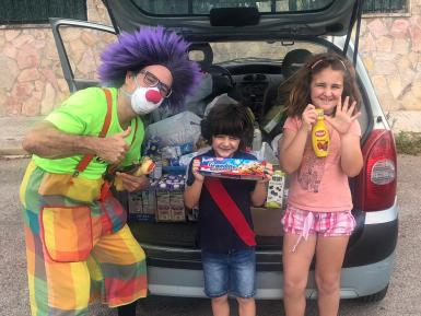 Geordie the clown and children donating food items.