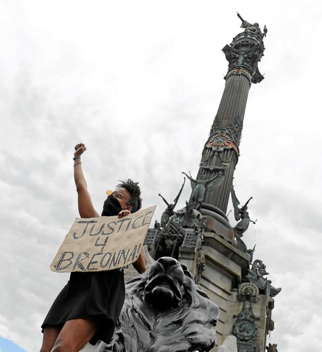 A protestor in front of Cristopher Columbus statue in Barcelona
