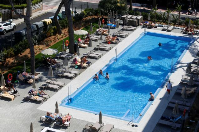 Tourists are seen in a hotel swimming pool in Playa de Palma.