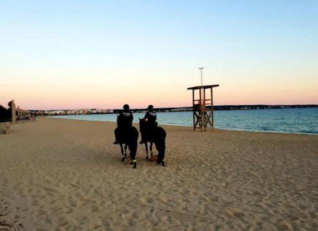 Police monitor closed beaches in Palma.