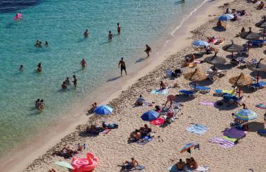 People sunbathe in Portals Nous beach.