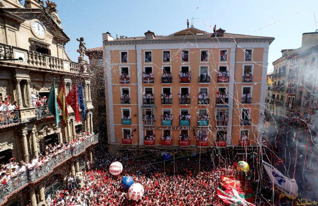 Revellers hold up the traditional red scarves during the firing of 'chupinazo', which opens the San Fermin festival in Pamplona Spain.