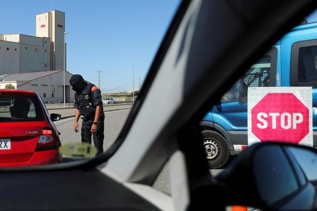 A Police officer checks the documents of people travelling on vehicles at the entrance of Lleida after Catalonia's government imposed new restrictions to control a new coronavirus disease outbreak in Lleida.