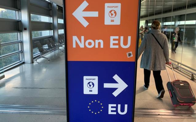 Passengers walk past a sign directing them to specific lines for EU and non EU passports as they arrive at Dublin Airport in Ireland.