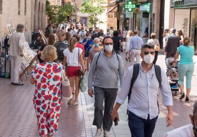 People walking through the streets of Palma wearing masks.