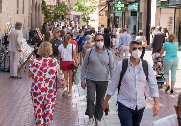 People walking through the streets of Palma wearing masks