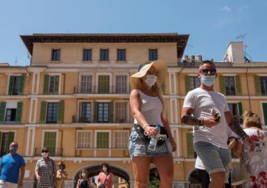People walking wearing face masks in the Plaza Major in Palma.