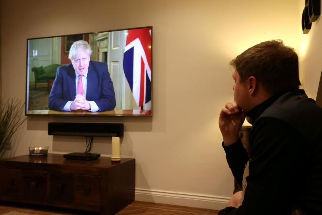A man watches British Prime Minister Boris Johnson's press conference