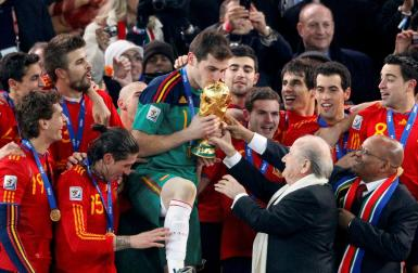 FIFA President Sepp Blatter (2nd R) and South African President Jacob Zuma (R) hand the World Cup trophy to Spain's team captain Iker Casillas (C) during the award ceremony at Soccer City stadium in Johannesburg July 11, 2010.